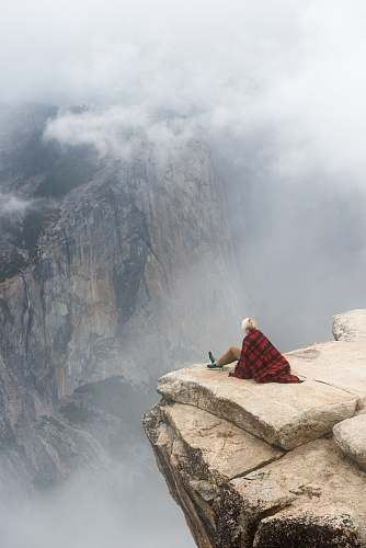 person person sitting on cliff under cumulus cloud human