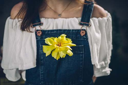 person person wearing overalls with yellow petaled flowers on pocket jeans