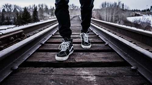 person person wearing pair of black-and-white Vans Old Skool shoes walking on brown train tracks during winter human