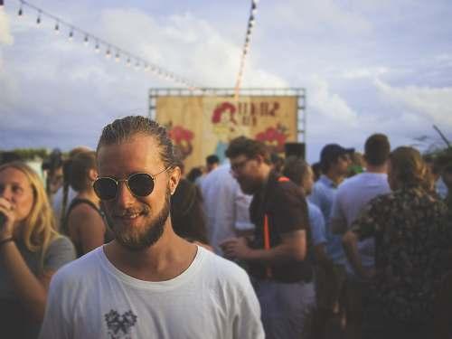 human person wearing white crew-neck shirt beside crowd crowd