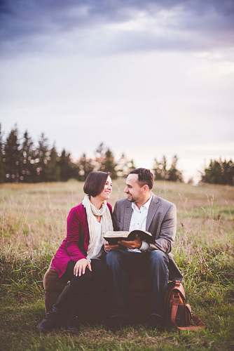 photo person photo of man reading book to woman under grey cloudy sky couple free for commercial use images