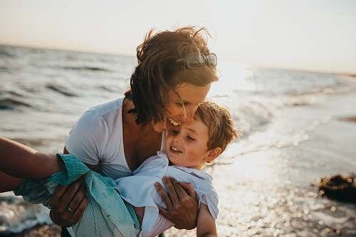 human photo of mother and child beside body of water family