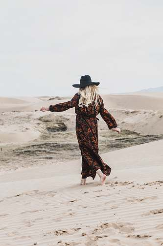 person photo of person wearing brown and orange floral maxi dress walking barefooted along deserted land woman