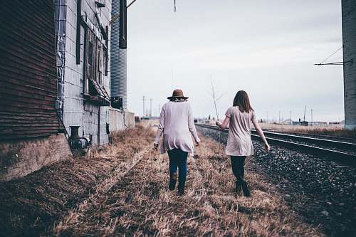 person photo of two persons walking along railway human