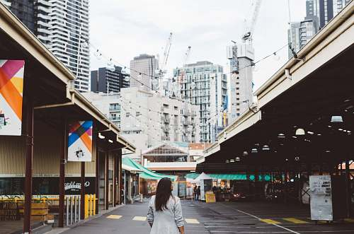 person photo of woman standing on roadway between buildings melbourne
