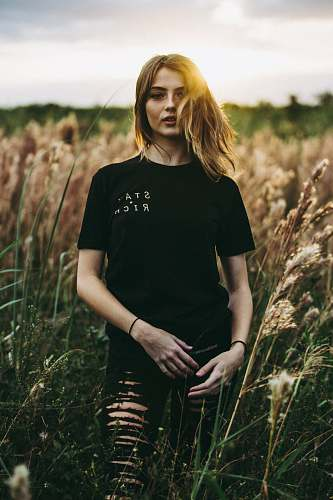 human selective focus photography of black crew-neck t-shirt and distressed black bottom standing on brown wheat field during daytime woman