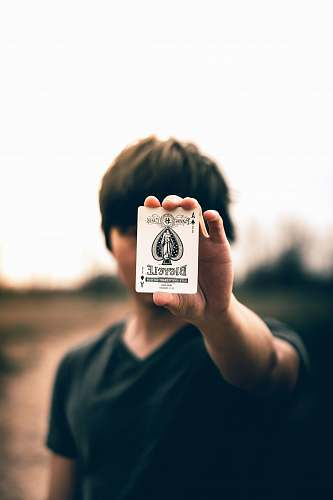 person selective focus photography of person holding ace of spades card human