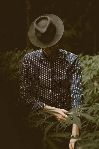 person shallow focus photography of man standing while folding his sleeve hat
