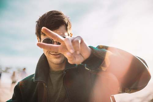 person shallow focus photography of smiling man doing peace sign human