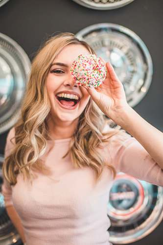 woman shallow focus photography of woman holding doughnut girl