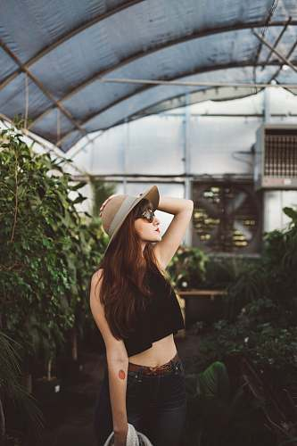 sunglasses shallow focus photography of woman posing while holding her hat at the garden plant