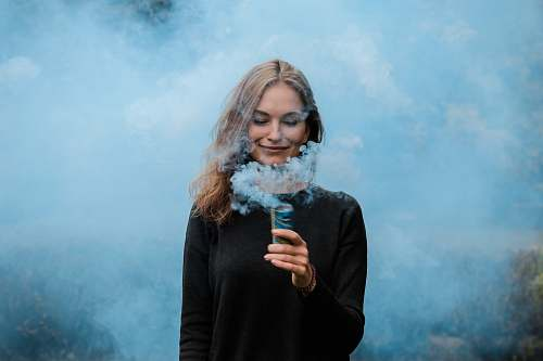 person shallow focus photography of woman surrounded by smoke woman