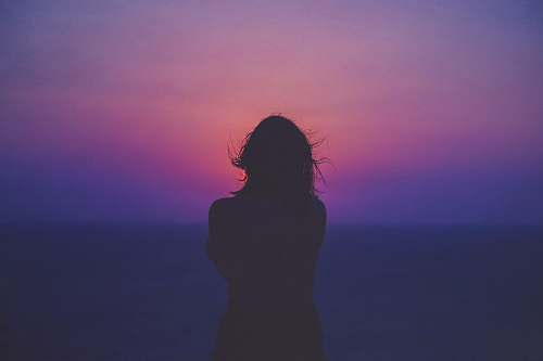 person silhouette of a woman with pink and purple sky silhouette