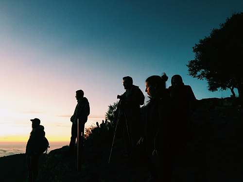 human silhouette of group of people standing on hill silhouette