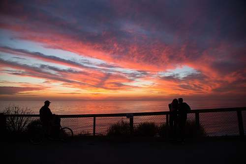 silhouette silhouette of people near cliff railings at distance to wide body of water during golden hour sunrise