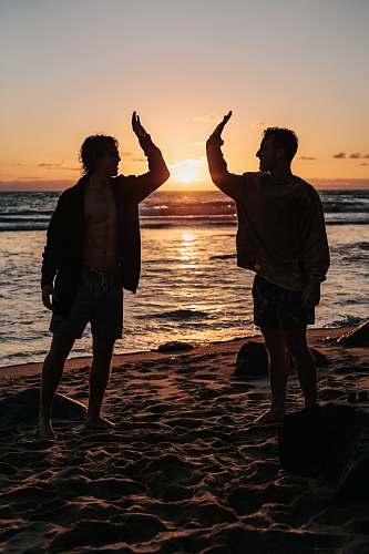 person silhouette of two mens near seashore about to high five during sunset human