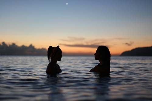 silhouette silhouette of two woman face to face in body water sea