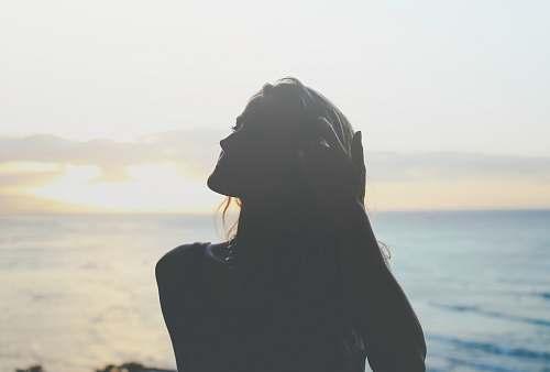 sky silhouette of woman across sea photo beach