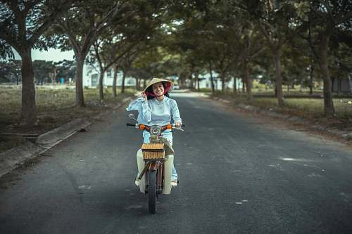 person smiling woman riding scooter on road riding