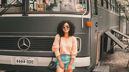 person smiling woman standing in front of Mercedes-Benz bus human