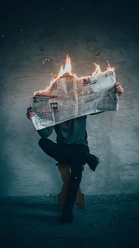 fire surrealism photography of person reading news paper in fire while sitting on stool flame