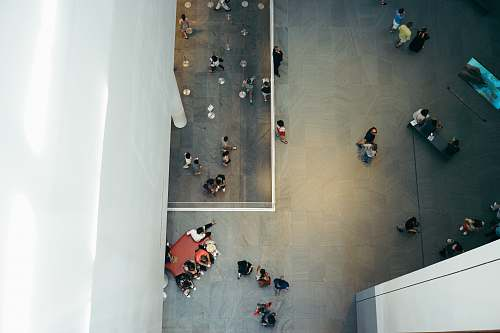 sit top-view photography of people beside white concrete building aerial