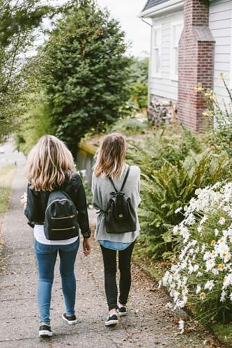 girl two ladies walking on sidewalk with black backpacks blonde