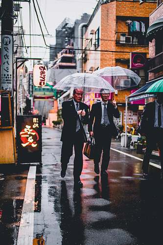umbrella two men in black suit holding transparent umbrellas walking in the street canopy