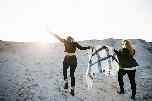 person vignette photography of two woman holding scarf walking on sand female