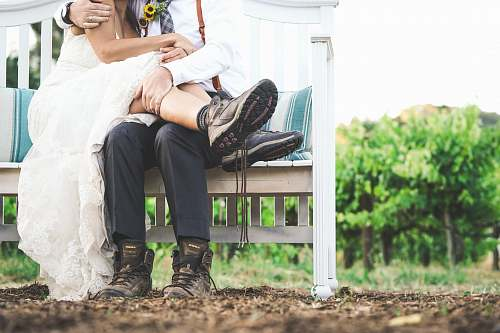 wedding woman and man sitting on white wooden bench human