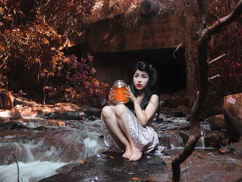 photo girl woman carrying glass jar while sitting on boulder beside flowing river behind brown bridge under shade of tree at daytime woman free for commercial use images