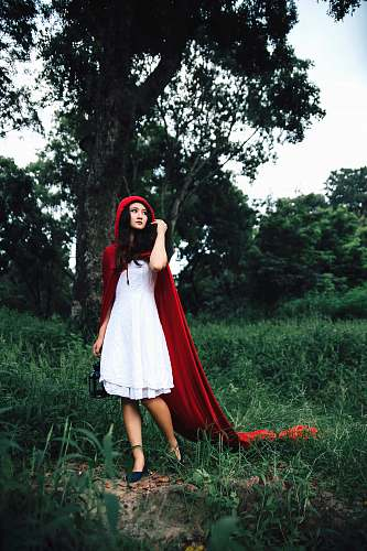 human woman cosplaying little riding hood near tree person