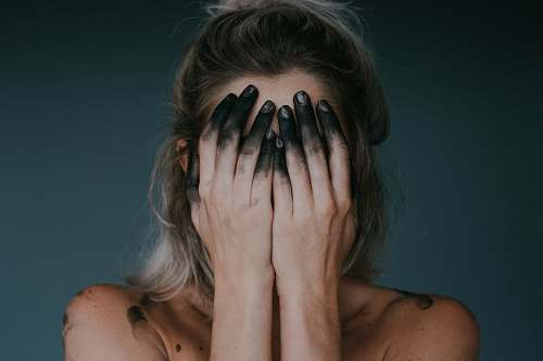 person woman covering face with both hands closeup photography human