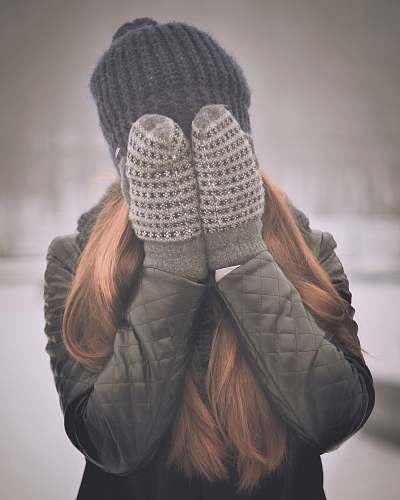 person woman covering her face mittens
