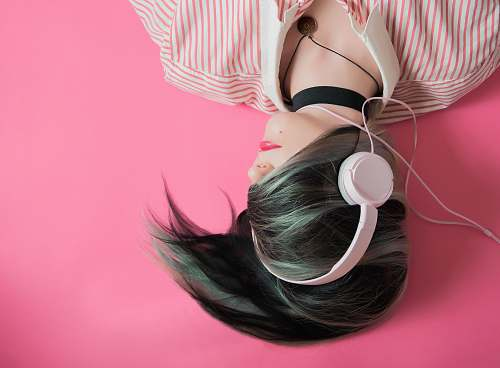 pink woman covering her hair and wearing headphones girl