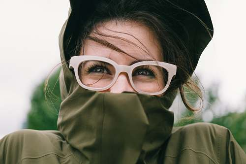 person woman covering mouth with green turtleneck top glasses