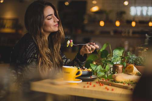 person woman holding fork in front table food
