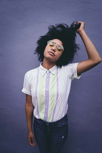 hair woman holding her hair near white concrete wall afro hairstyle