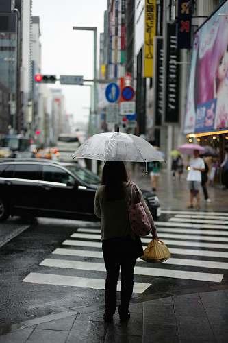 human woman holding umbrella standing on pedestal lane umbrella