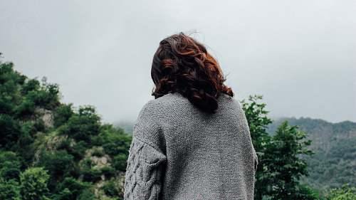 person woman in gray sweater standing in front of trees during daytime back