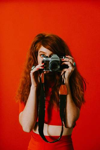 person woman in red top and bottoms holding Pentax camera human