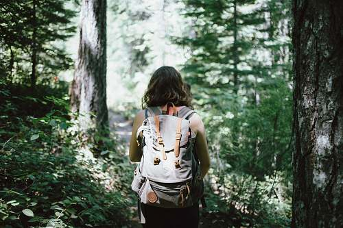 nature woman in sleeveless top and backpack surrounded by trees during daytime forest