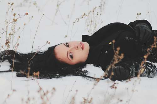 person woman laying on snowy ground woman