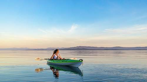 boat woman on green and white kayak holding yellow oar under white clouds and blue sky kayak