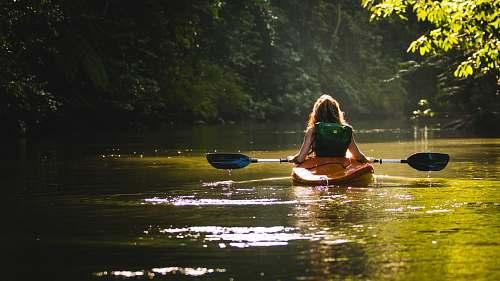 canoe woman on kayak on body of water holding paddle kayak