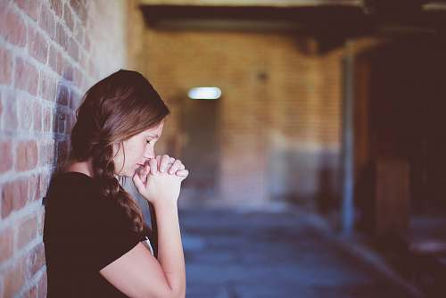 woman woman praying while leaning against brick wall girl