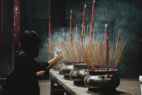person woman putting incense sticks on pot incense