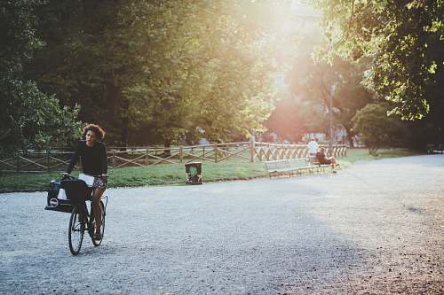 person woman riding bicycle on park during daytime bicycle