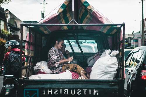 person woman seating on drop side truck truck