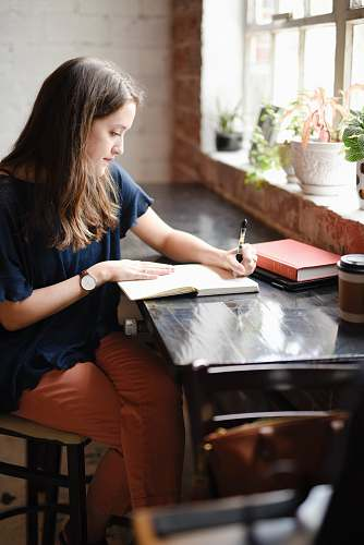 person woman sitting in front of black table writing on white book near window human